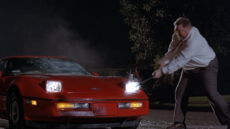 "John Goodman smashing a car with a crowbar in ""The Big Lebowski."""