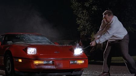 "John Goodman smashing a car with a crowbar in ""The Big Lebowski."""